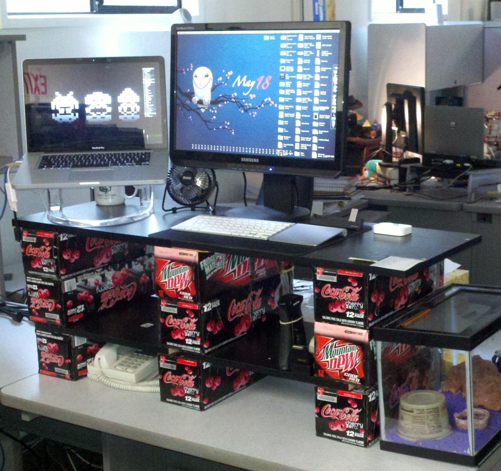 Boards stacked on top of soda can boxes to make a DIY standing desk